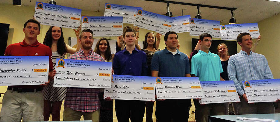 The sons and daughters of Fairfield police officers show off the $1,000 college scholarship checks they received Thursday. Photo: Genevieve Reilly / Fairfield Citizen