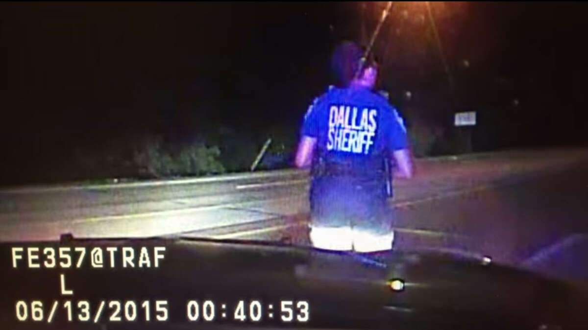 """A Dallas County Sheriff's Office dashboard camera shows an officer deploying """"stop sticks"""" early June 13, 2015 to stop the armored van of James Boulware, who authorities say fired upon Dallas Police headquarters just moments before."""