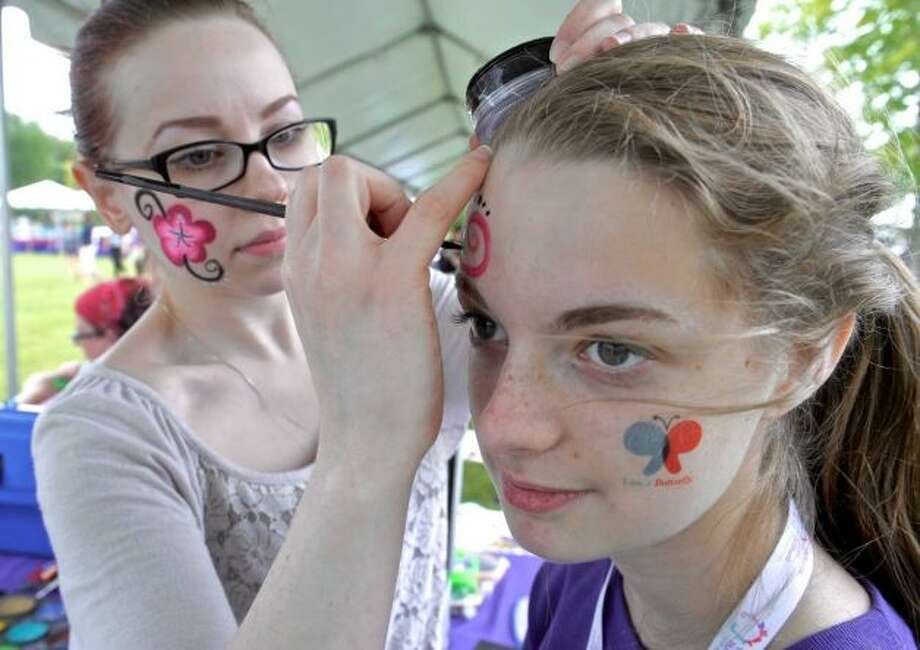 """Kate Moyle, 16, of Newtown, has a design painted on her face by Brenda Marousek during the Catherine Violet Hubbard Foundation's second annual """"Butterfly Party"""", a community event honoring Catherine Violet Hubbard, one of the students lost in the Sandy Hook Elementary School shooting. Saturday, June 6, 2015, in Newtown, Conn. Moyle was a volunteer at the event and Marousek is with Kaleidoscope art + entertainment in Hartford Photo: H John Voorhees III / Hearst Connecticut Media"""