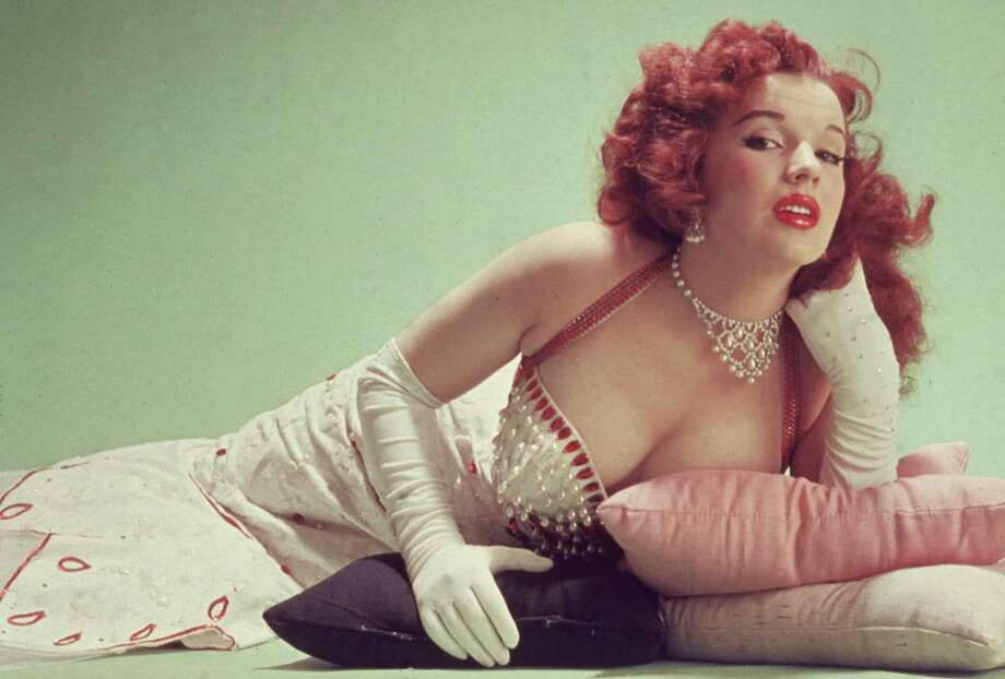 circa 1955:  Studio portrait of Blaze Starr, reclining on pillows on the floor, wearing a red-trimmed white dress and white elbow-length gloves. Photo: Hulton Archive, Getty Images / Archive Photos