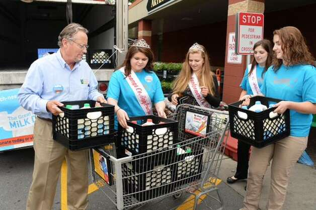 State Agriculture Commissioner Richard Ball and state dairy princesses load a truck with milk for the Regional Food Bank on Tuesday, June 16, 2015, at Price Chopper in Schenectady. (John Carl D'Annibale/Tiimes Union)