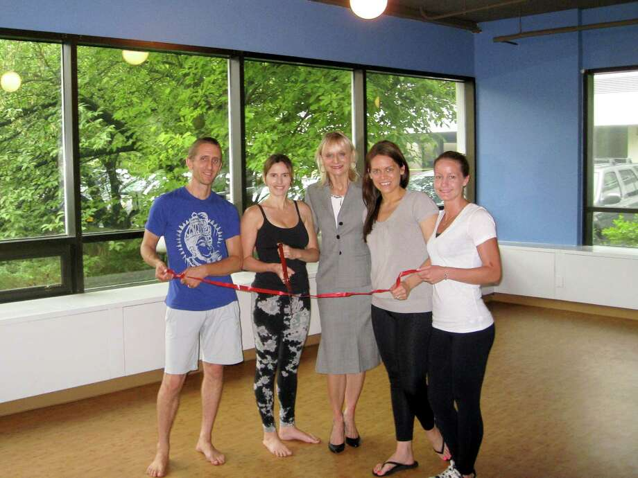 From left to right, Kaia Yoga studio owners Stan Woodman and Gina Norman, Chamber of Commerce Director Marcia O'Kane, and two instructors at Kaia Yoga pose for a ceremonial ribbon cutting at the opening of the newest Kaia studio in Old Greenwich. Photo: Contributed