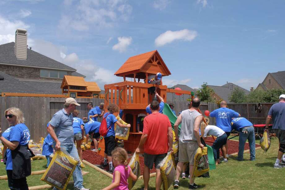 Volunteers put the finishing touches on the new playset for 3-year old Nolan Day. The Roc Solid Foundation surprised Nolan Day with a brand-new playset in his backyard. / Freelance