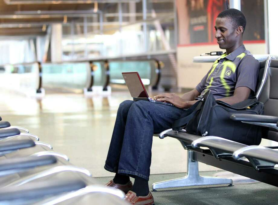 Ayo Deji Oyewo works on his laptop while waiting to catch a plane in Terminal D at the Houston Intercontinental Airport, Monday, Jan. 28, 2013, in Houston. Houston Airport System working to develop a free Wifi network at IAH and HOU airports, which are some of the last in Texas to not offer free wifi. ( Karen Warren / Houston Chronicle ) Photo: Karen Warren, Staff / © 2013 Houston Chronicle