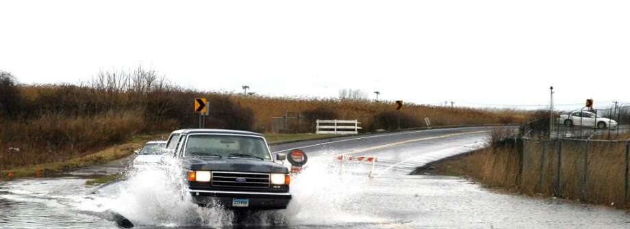 Traffic slows to drive through a flooded portion of Main Street in Stratford, Sunday, March 14, 2010. The heavy rain and high tides drove the water up in the wetlands and the runway approach at Sikorsky Airport. Photo: Phil Noel / Connecticut Post