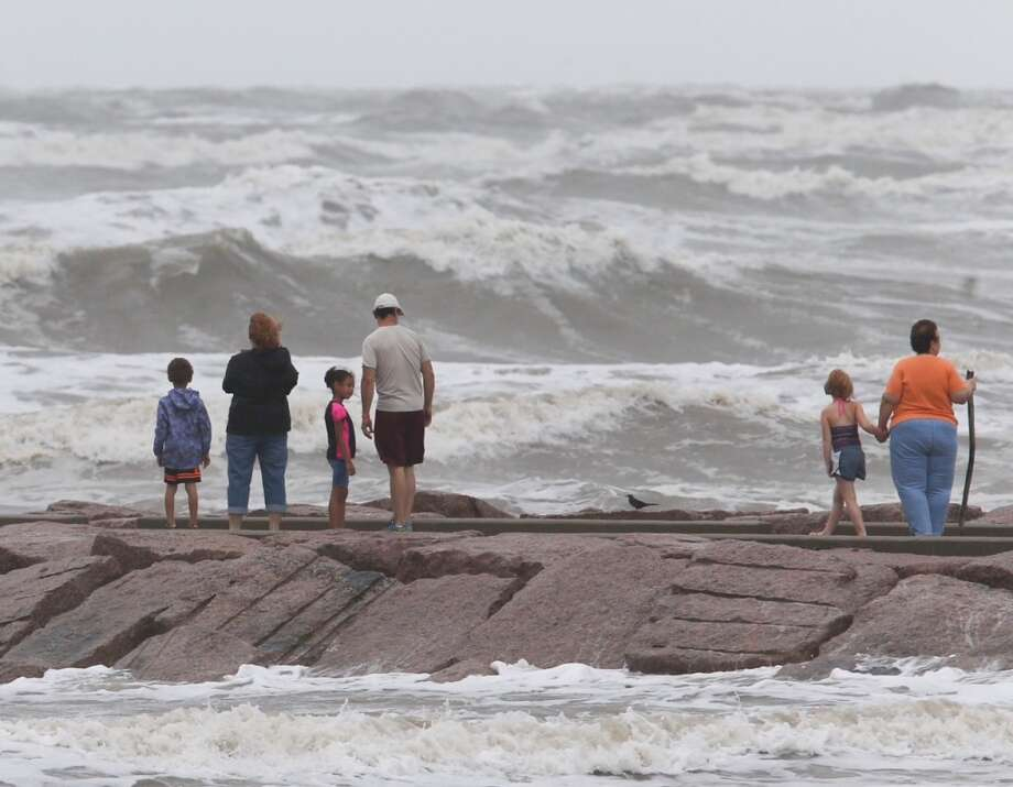 People stand on a rock groin in Galveston along Seawall Boulevard as Tropical Storm Bill approaches the Texas coast. (June 16, 2015) Photo: James Nielsen/Houston Chronicle