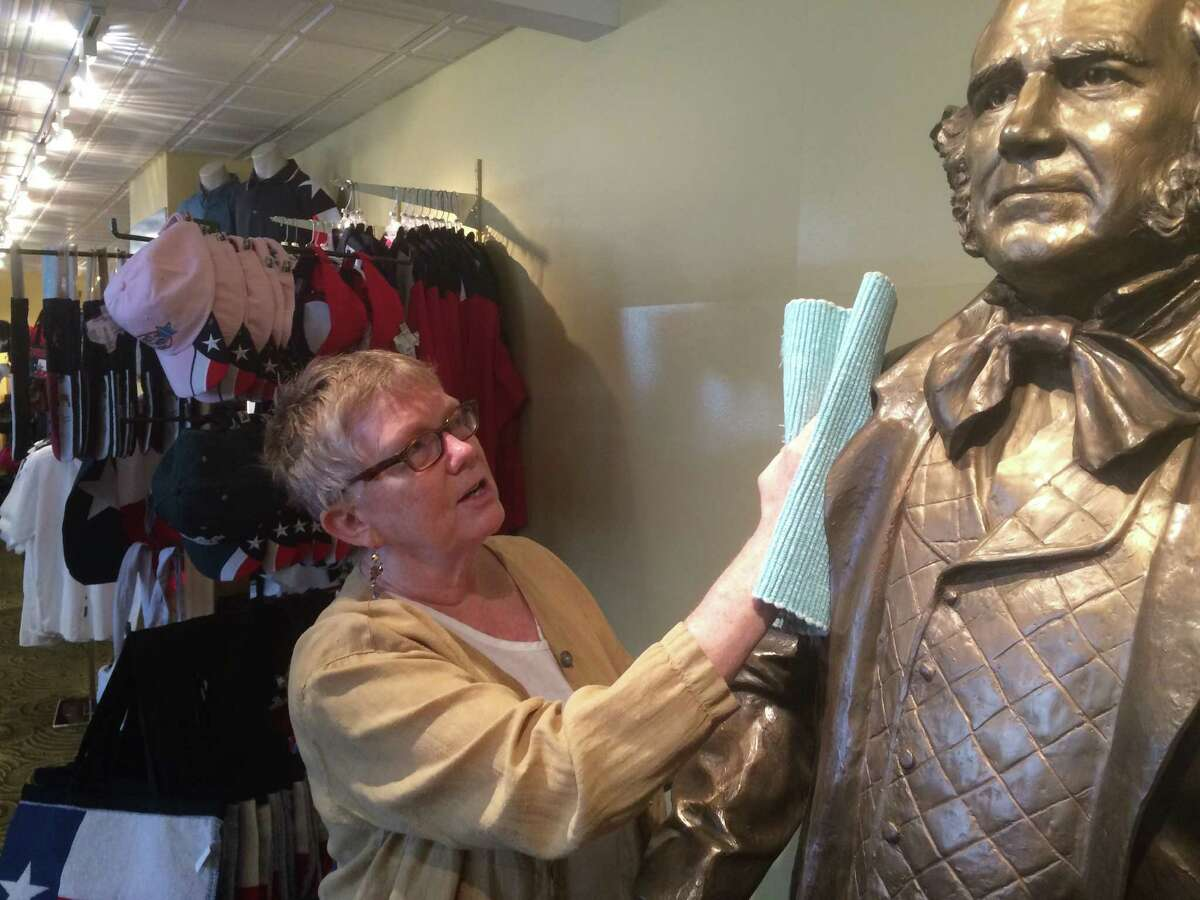 Cherry Eno, director of the Houston Visitors Center, polishes a statue of Sam Houston in the center's new location at 1300 Avenida de las Amercias, across from the George R. Brown Convention Center.