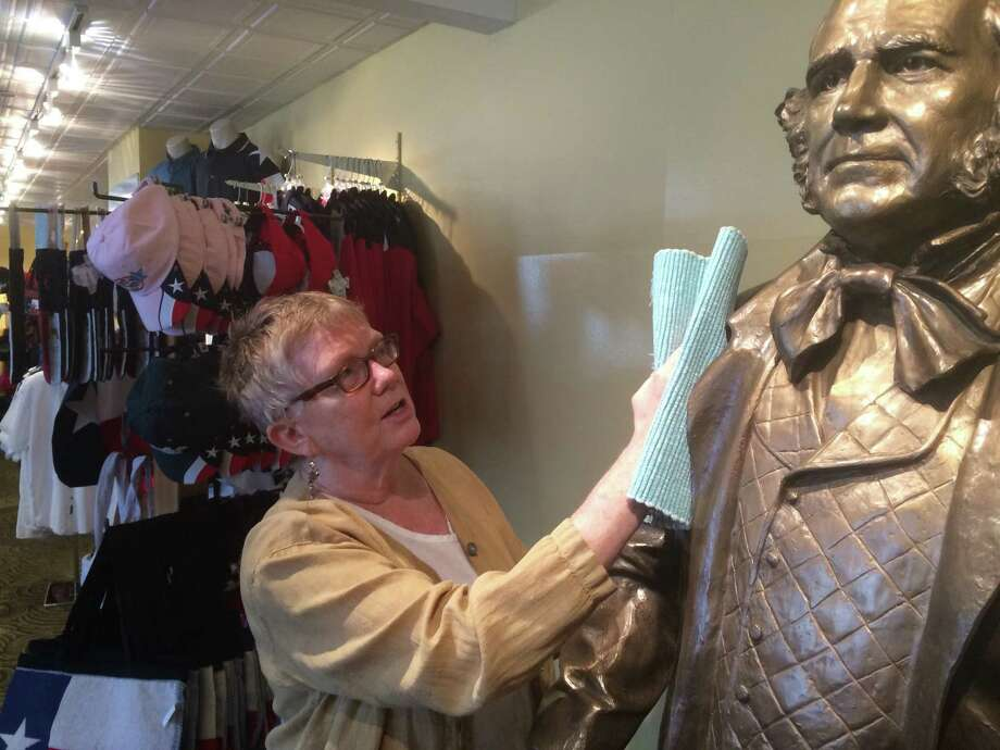 Cherry Eno, director of the Houston Visitors Center, polishes a statue of Sam Houston in the center's new location at 1300 Avenida de las Amercias, across from the George R. Brown Convention Center. Photo: Houston First Corp.