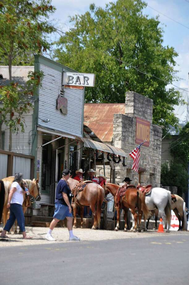 Riders tie horses to the hitching post outside the 11th Street Bar in Bandera. Photo: Janet Terry / San Antonio Express-News