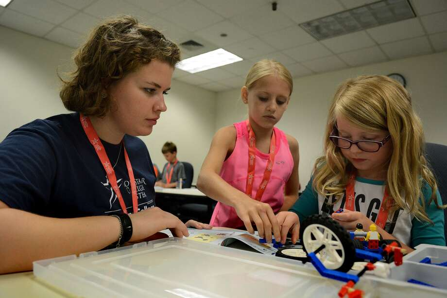 Camp aide Rene Schulze, 19, from left, a sophomore Urban Planning major at Texas A&M Univ., and campers Gabby Martin, 8, a 4th grader at Lamar Elem., and Ashley Pickering, 8, a 3rd grader at Coulson Tough Elem., team up on a Lego project during the Discovery College Summer Camp at Lone Star College - Montgomery on Monday, June 15, 2015. (Photo by Jerry Baker/Freelance) Photo: Jerry Baker, Freelance