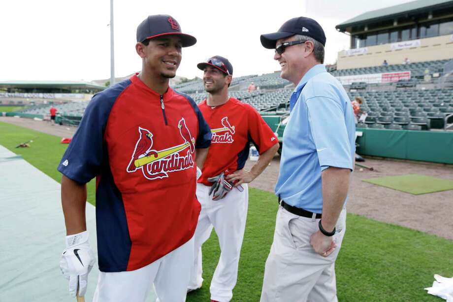 In this Feb. 25, 2013, file photo, Houston Astros general manager Jeff Luhnow, right, talks to St. Louis Cardinals center fielder Jon Jay, left, and second baseman Daniel Descalso before an exhibition spring training baseball game in Jupiter, Fla. Major League Baseball says it is cooperating with a federal investigation into an illegal breach of the Astros' internal operations database, amid a report that the Cardinals were responsible for the hack. Photo: Julio Cortez /Associated Press / AP