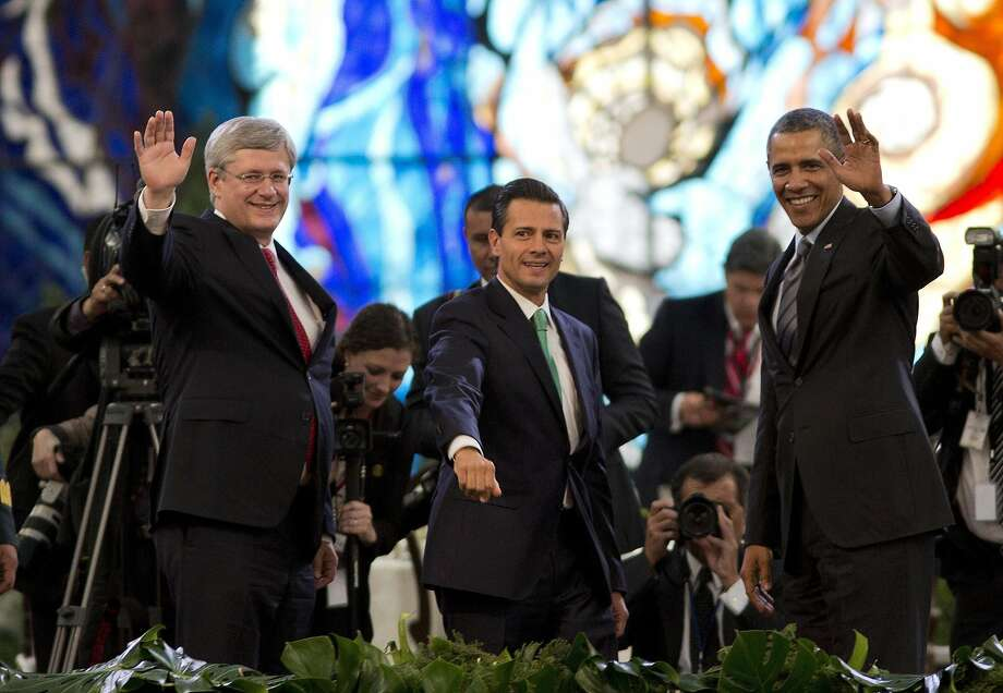 Prime Minister of Canada Stephen Harper, left, Mexico's President Enrique Pena Nieto, center, and President Barack Obama pose for photos inside the Cosmovitral stained glass botanical garden at the North American Leaders Summit in Toluca, Mexico, Wednesday, Feb. 19, 2014. The leaders of the three North American Free Trade Agreement (NAFTA) nations met in part to highlight the economic cooperation that has grown since NAFTA joined the U.S., Canada and Mexico 20 years ago. (AP Photo/Eduardo Verdugo) Photo: Eduardo Verdugo, Associated Press