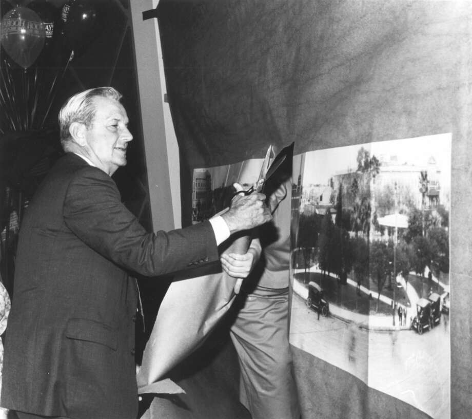 Charles B. Cheever Jr., senior chairman of the Broadway National Bank, cuts through a copy of a panoramic picture of Alamo Plaza that was taken by the late E. O. Goldbeck, to open the new branch of the bank in the downtown area. Photo: Express-News File Photo / SAN ANTONIO EXPRESS-NEWS