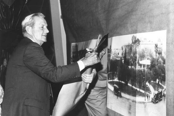 Charles B. Cheever Jr., senior chairman of the Broadway National Bank, cuts through a copy of a panoramic picture of Alamo Plaza that was taken by the late E. O. Goldbeck, to open the new branch of the bank in the downtown area.