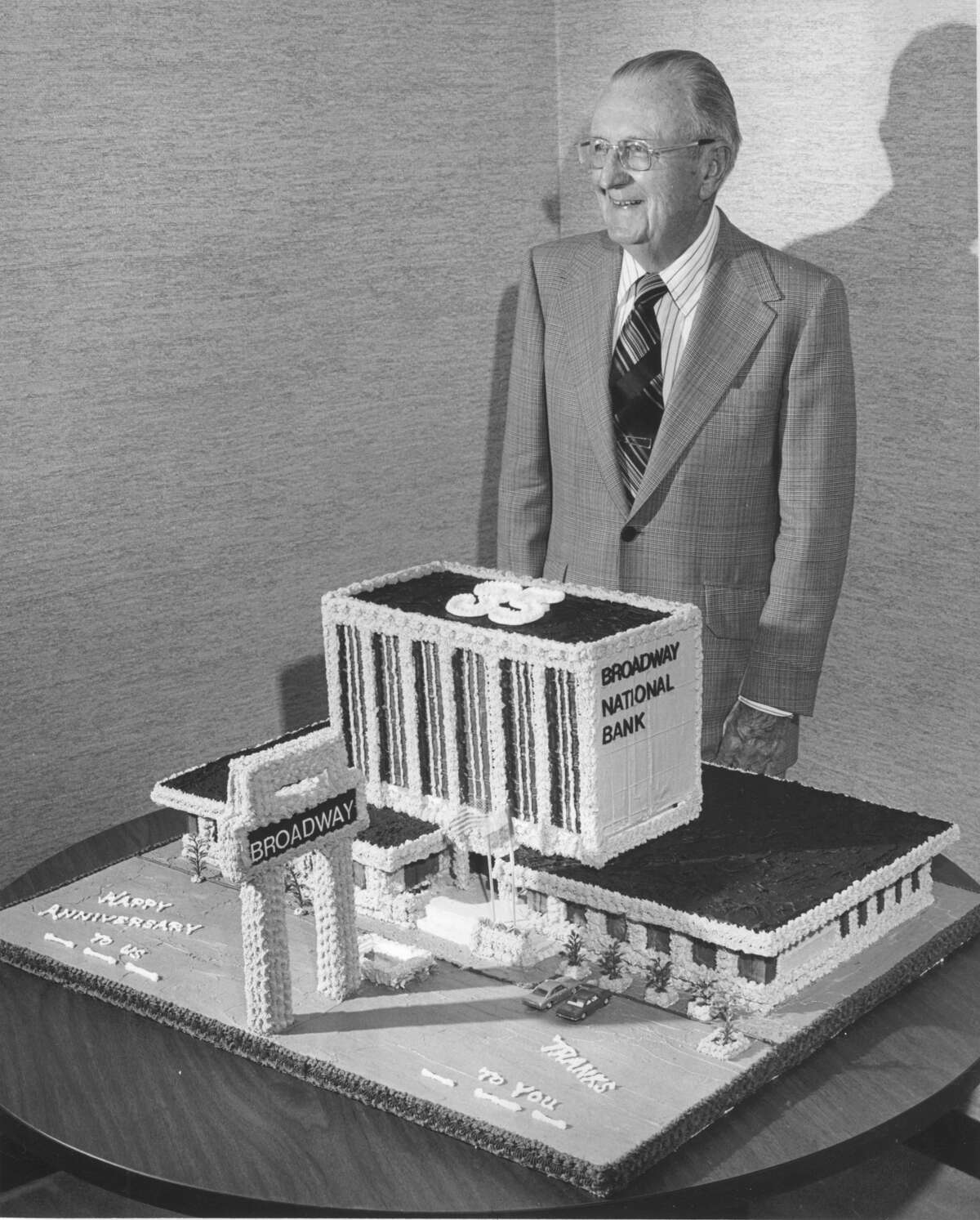 Col. C. E. Cheever poses near the bank-shaped cake for the Broadway National Bank's 35th anniversary in 1976.