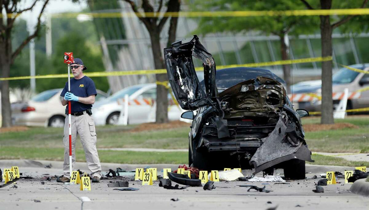 FILE - In this May 4, 2015 file photo, FBI crime scene investigators document evidence outside the Curtis Culwell Center in Garland, Texas. A Phoenix-area man has been charged with helping plan the attack on a provocative Texas cartoon contest featuring depictions of the Prophet Muhammad that ended with the two shooters' deaths last month. An indictment filed in federal court in Phoenix alleges that Abdul Malik Abdul Kareem hosted the gunmen in his home beginning in January and provided the guns they used in the May 3 shooting. (AP Photo/Brandon Wade,File)