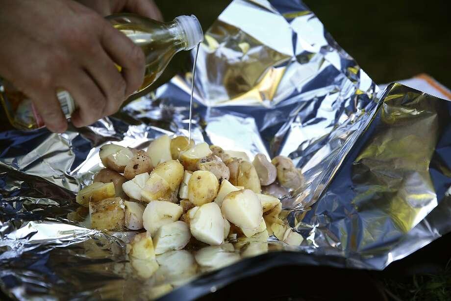 "Chef Louis Maldonado of Spoonbar seasons his potato ""hobo packs"" before placing them on the grill. Photo: Liz Hafalia, The Chronicle"