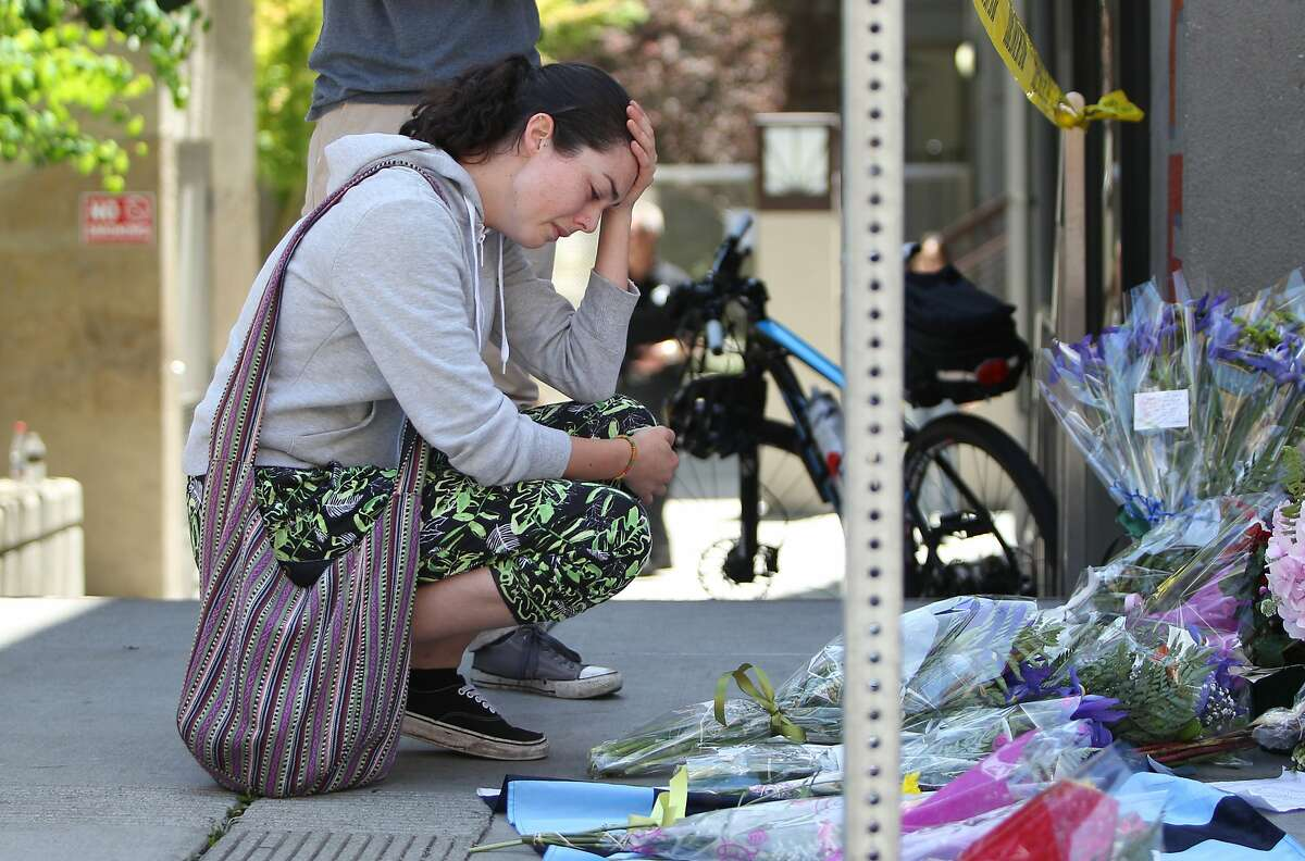 A woman (who declined to be identified) mourns at a makeshift memorial shrine by 2020 Kittredge Street in Berkeley, California, on Tuesday, June 16, 2015. A balcony attached to the apartment building collapsed in the early hours of Tuesday, killing 6 and injuring others.