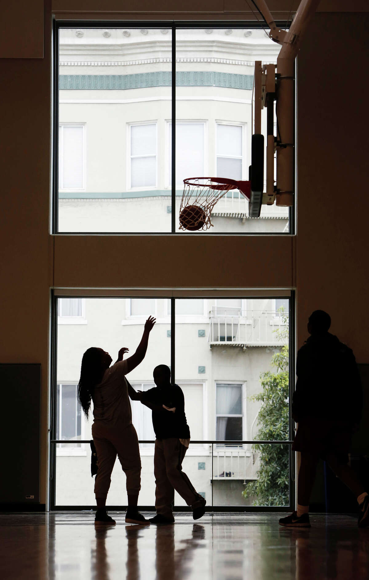 Children play on the basketball court in front of the ample windows in the gym of the impressive new Boys & Girls Club building on Fulton Street near Civic Center.
