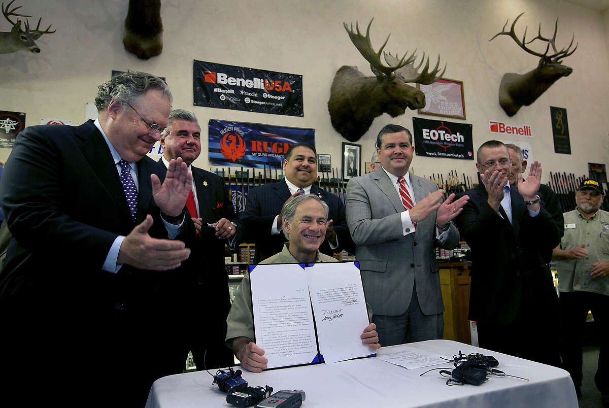 Texas Gov. Greg Abbott signs into law bills letting Texans carry concealed handguns on college campuses and openly carry them virtually everywhere else at Red's Indoor Range in Pfulgerville, Texas, Saturday, June 13, 2015. (Ralph Barrera/Austin American-Statesman via AP) AUSTIN CHRONICLE OUT, COMMUNITY IMPACT OUT, INTERNET AND TV MUST CREDIT PHOTOGRAPHER AND STATESMAN.COM, MAGS OUT