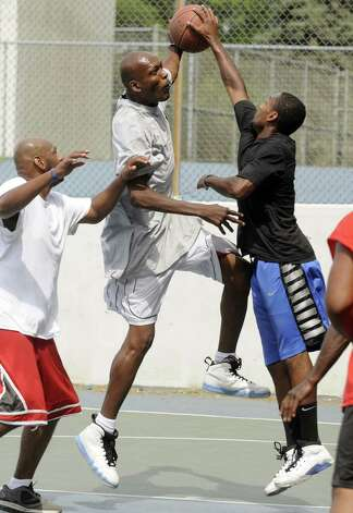 Calvin Danzy, center, drives to the basket during a game of pickup basketball played every weekend on the courts at Washington Park Saturday, June 30, 2012, in Albany N.Y. (Michael P. Farrell/Times Union archive) Photo: Michael P. Farrell / 00018255A