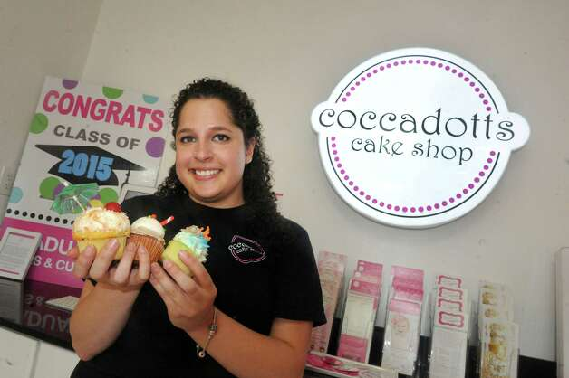 Jennifer Gavens holds three of the new summer flavors of cupcakes, pi–a colada, root beer float and caramel & sea salt at Coccadotts bakery on Tuesday June 16, 2015 in Albany, N.Y.  (Michael P. Farrell/Times Union) Photo: Michael P. Farrell / 00032310A