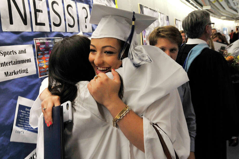 Merlyn Tejada, left, and Olga Papaeconomou embrace following the commencement ceremony at Darien High School in Darien, Conn., on Tuesday, June 16, 2015. Photo: Jason Rearick / Hearst Connecticut Media / Stamford Advocate