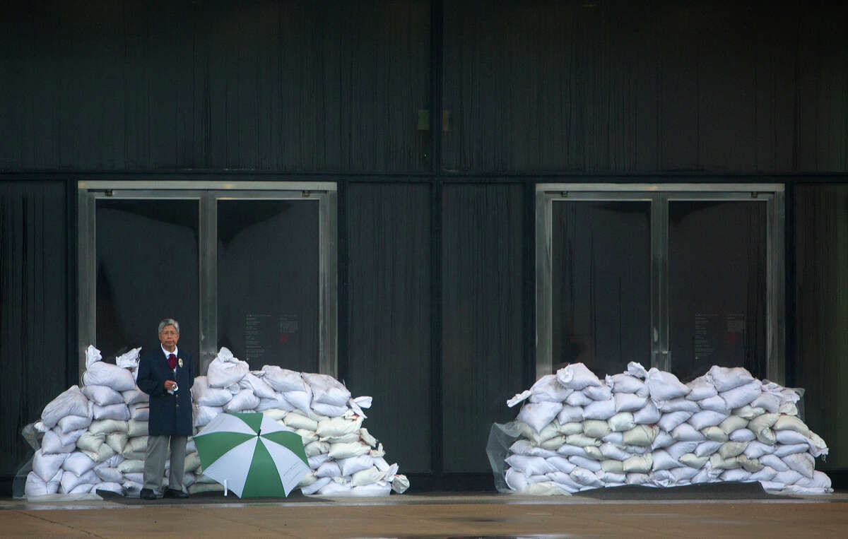 A security guard at the Museum of Fine Arts, Houston stands in front of sandbags that were set up as a precaution against flooding.