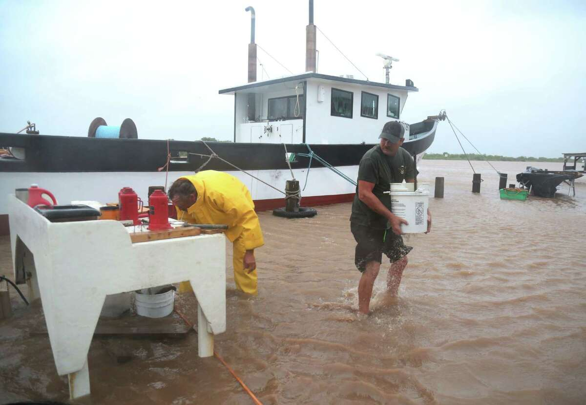 Kirk Vossler and John Bryant move items away from Colorado River floodwaters in Matagorda.