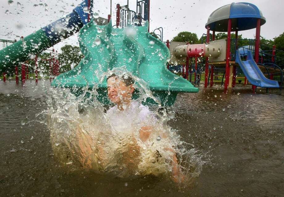 Seven-year-old Devin Vincent splashes down from a slide on a flooded playground at Clear Lake Park in southern Harris County, Texas, Tuesday, June 16, 2015.  Area creeks and bayous were flooded by rains and the tidal surge from Tropical Storm Bill.  Tropical Storm Bill moved slowly over inland Texas on Tuesday, bringing another round of heavy rains to a state weary from recent deadly floods, evacuations and washed-out roads. (Stuart Villanueva/The Galveston County Daily News via AP) Photo: Stuart Villanueva, MBR / Associated Press / The Galveston County Daily News