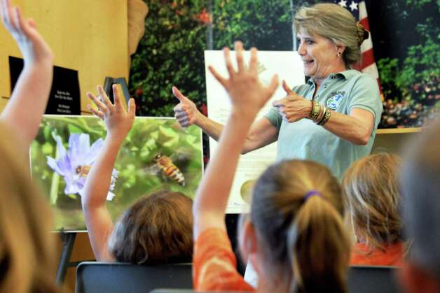 Director of ENCON's Division of Fish, Wildlife, and Marine Resources Patricia Riexinger gives two thumbs up to 2nd graders from Berne Knox Westerlo Elementary School as they answer questions about the environment during a visit to the Thacher Nature Center for Pollinator Protection Week Tuesday June 16, 2015 in Voorheesville, NY.  (John Carl D'Annibale / Times Union) Photo: John Carl D'Annibale / 00032297A