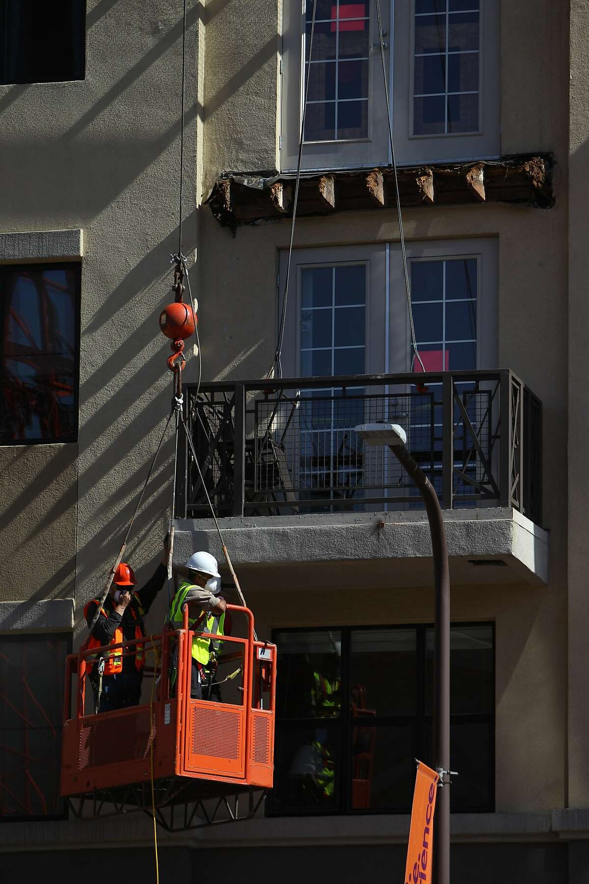 A balcony below the one that collapsed is worked on at 2020 Kittredge Street in Berkeley, California, on Tuesday, June 16, 2015. The collapse, which took place in the early hours of Tuesday, killed 6 and injured others.