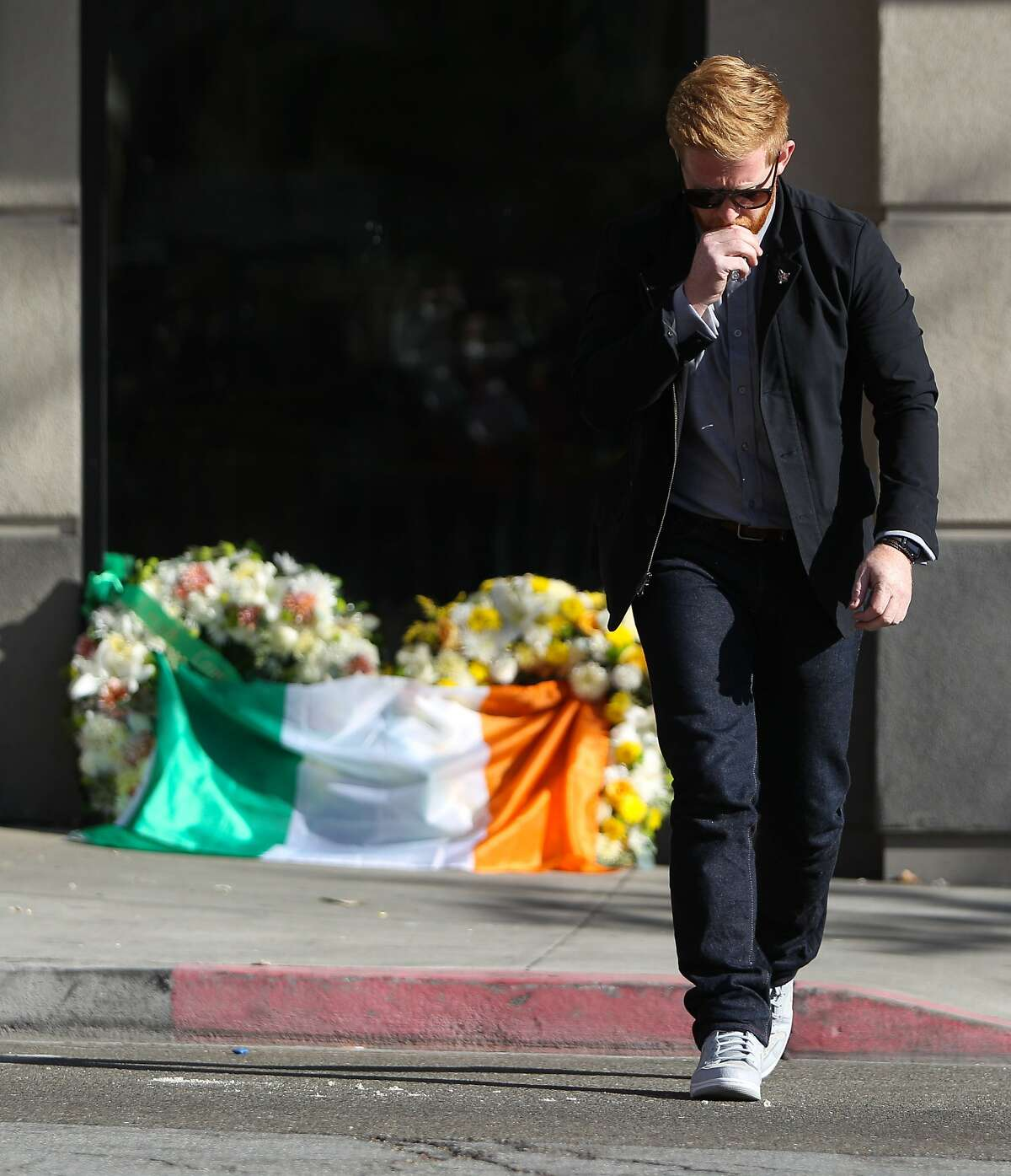 Neil Sands of Irish Network Bay Area departs after laying an Irish flag on wreathes in front of 2020 Kittredge Street in Berkeley, California, on Tuesday, June 16, 2015. The balcony collapse that occurred there killed 6 and injured others.