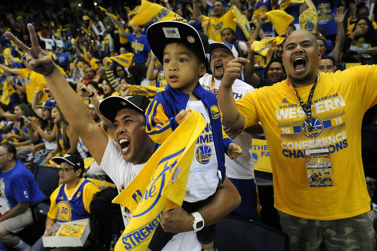Will Cristobal holds his son Liam Cristobal, 2, as they cheer with the crowd in the first quarter during an NBA Finals Game 6 Warriors Watch Party at Oracle Arena in Oakland, CA Tuesday, June 16, 2015.