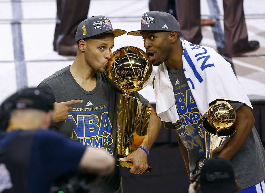 Golden State Warriors guard Stephen Curry, left, holds the championship trophy and Andre Iguodala holds the series MVP trophy as they celebrate winning the NBA Finals. Photo: Paul Sancya, Associated Press