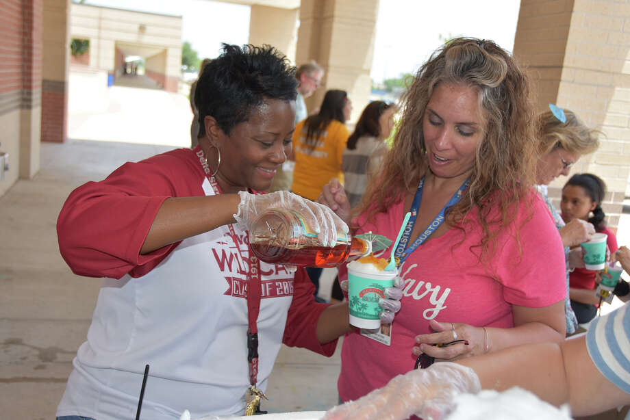 Cypress Woods High School assistant principal Andrea Lagard fills up a cup of shaved ice with Bahama Bucks syrup for bus driver April Selig. Photo: Cfisd