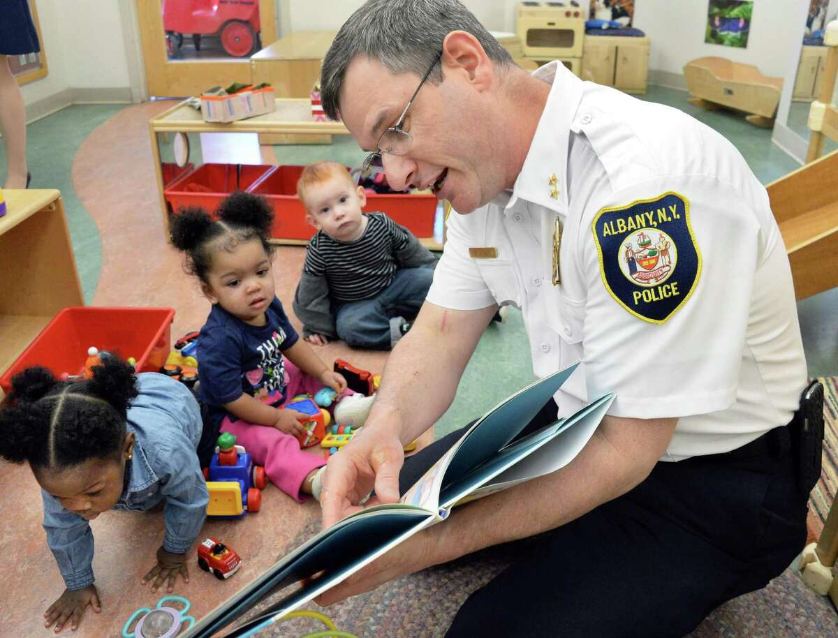 """Acting Chief Brendan Cox of the Albany Police Dept. reads to toddlers during the Club Fed Child Care Center's """"Our Family Reads!"""" project at the Leo O'Brien Federal Building Wednesday April 15, 2015 in Albany, NY. (John Carl D'Annibale / Times Union) ORG XMIT: MER2015041513161160"""