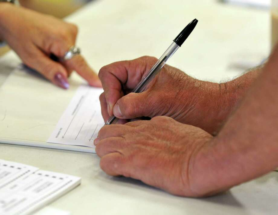 Menands resident, Archie Viger, signs in to vote Tuesday, June 16, 2015, at the Municipal Firehouse in Menands, N.Y. (Phoebe Sheehan/Special to the Times Union) Photo: PS / 00032279A