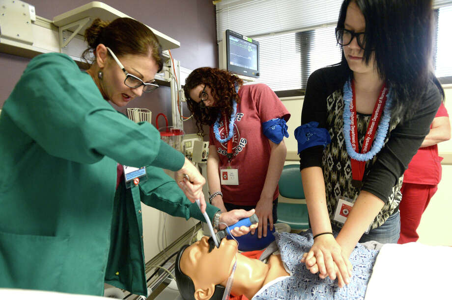Nurse Sandra Lucia demonstrates how to intimate a patient as students Lacy Harvey of Hardin-Jefferson (left) and Carley Britnell of Buna assist in treating a coding patient in the ICU during the Nightingale Experience's hands-on sessions at Christus St. Mary's Hospital in Port Arthur Friday.  Photo taken Friday, June 12, 2015  Kim Brent/The Enterprise Photo: Kim Brent / Beaumont Enterprise