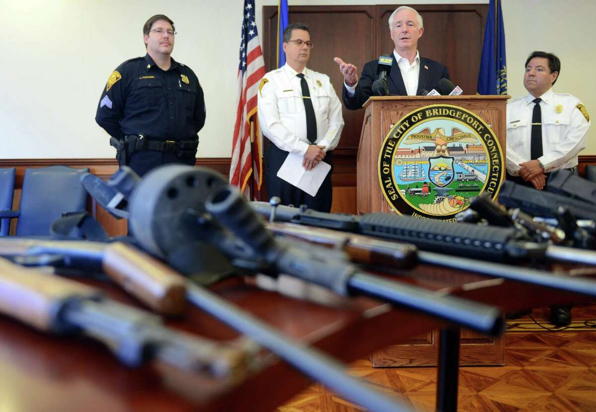 Bridgeport Mayor Bill Finch gestures to some of the guns obtained through the city's Gun Buyback program on Nov. 14, 2013, at the Margaret Morton Government Center.