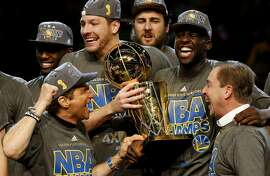 CLEVELAND, OH - JUNE 16:  Draymond Green #23 David Lee #10 and Andrew Bogut #12 of the Golden State Warriors celebrates with team owners Peter Guber and Joe Lacob and the Larry O'Brien NBA Championship Trophy after defeating the Cleveland Cavaliers 105 to 97 to win Game Six of the 2015 NBA Finals at Quicken Loans Arena on June 16, 2015 in Cleveland, Ohio. NOTE TO USER: User expressly acknowledges and agrees that, by downloading and or using this photograph, user is consenting to the terms and conditions of Getty Images License Agreement.  (Photo by Ezra Shaw/Getty Images)