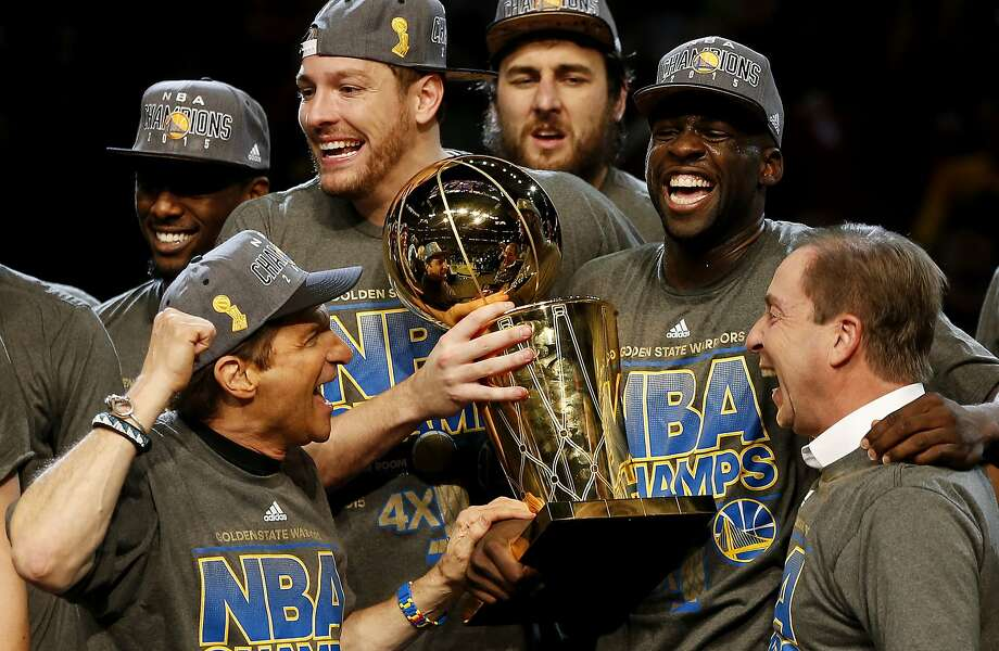 The Golden State Warriors and the team's co-owners, Peter Guber (left) and Joe Lacob, celebrate their victory Tuesday over the Cleveland Cavaliers, which gave them and Oakland their first NBA champion ship in 40 years. Photo: Ezra Shaw, Getty Images