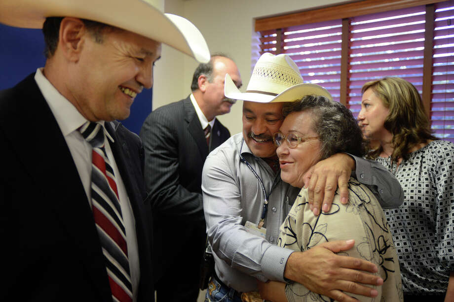 Former Texas Ranger and current chief of police in Edinburg, Rolando Castaneda smiles, left, as Cameron County Sheriff's Department Lt. Carlos Garza hugs Hermila Garcia after a news conference at the Cameron County district attorney's officer in May 2014. Hermila Garcia's late daughter, Hermila Hernandez, was murdered by Amit Livingston, who pleaded guilty in 2005, but became a fugitive in 2007. Livingston was apprehended in India and will soon be extradited to Texas. Photo: Brad Doherty /The Brownsville Herald Via Associated Press / AP