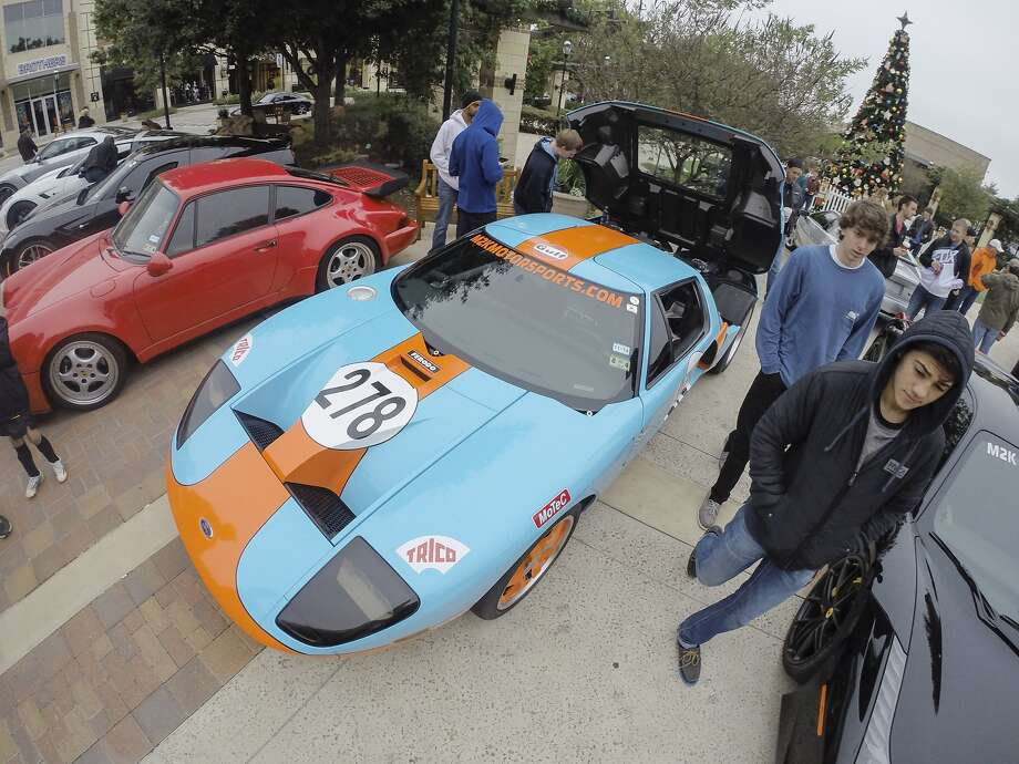 Car enthusiasts check out a Ford GT owned by Mark Hidacker of M2K Motorsports. The car holds the current world record for the Texas Mile with a top speed of 278 mph. The cars were on display at the Ride n' Shine Car Show held at La Centerra in Katy on November 15, 2014. Photo: Diana L. Porter, Freelance / © Diana L. Porter