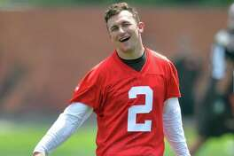 Cleveland Browns quarterback Johnny Manziel laughs as he comes off the field during minicamp in Berea, Ohio, Tuesday, June 16, 2015.