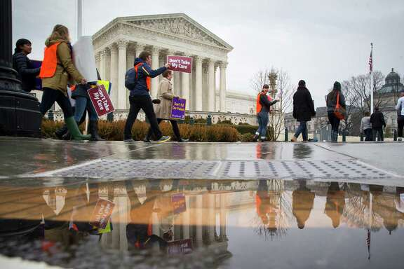 FILE-- Protesters outside the Supreme Court on Wednesday morning in Washington, March 4, 2015. Democrats and Republicans say a clause in the Affordable Care Act affecting subsidies, now before the court, was an inadvertent product of a sloppy merging of versions.