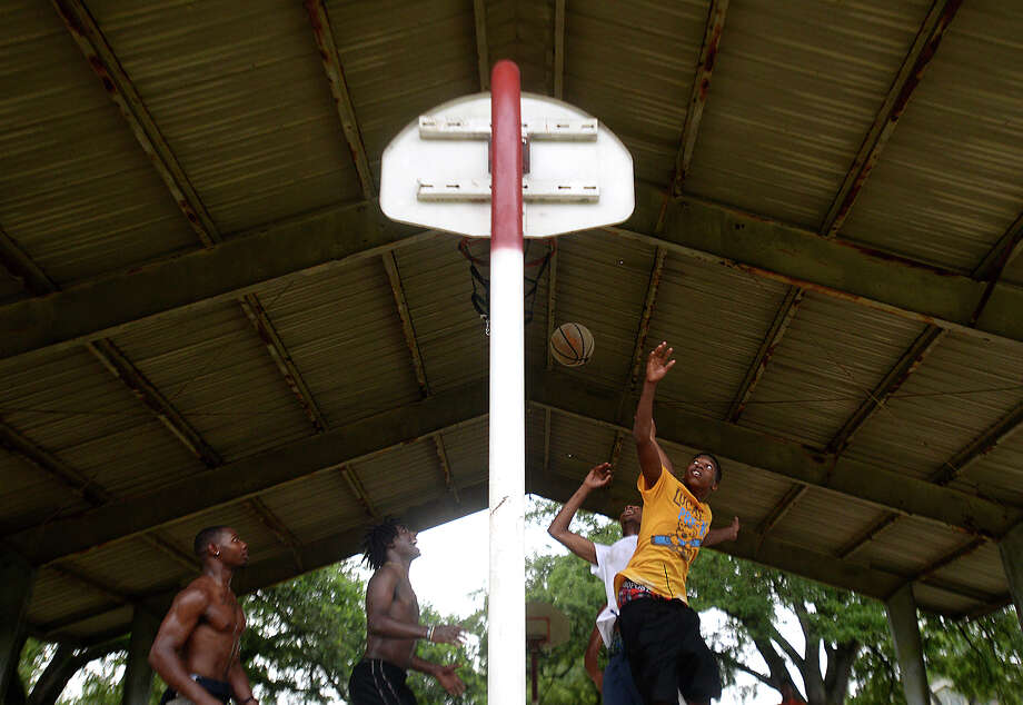 As cloud bursts continued to provide periods of heavy showers throughout the evening Tuesday, a game of basketball continued beneath the covered court at Magnolia Park. The region saw peripheral effects of Tropical Storm Bill as it made its way up the Gulf. Photo taken Tuesday, June 16, 2015 Kim Brent/The Enterprise Photo: Kim Brent / Beaumont Enterprise