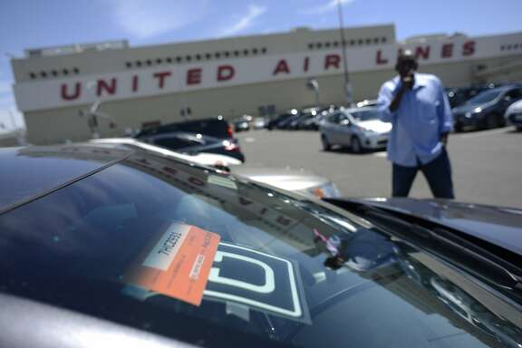 An Uber driver smokes a cigarette as he waits in a parking lot near SFO Airport in San Francisco, California, on Wednesday, June 17, 2015.