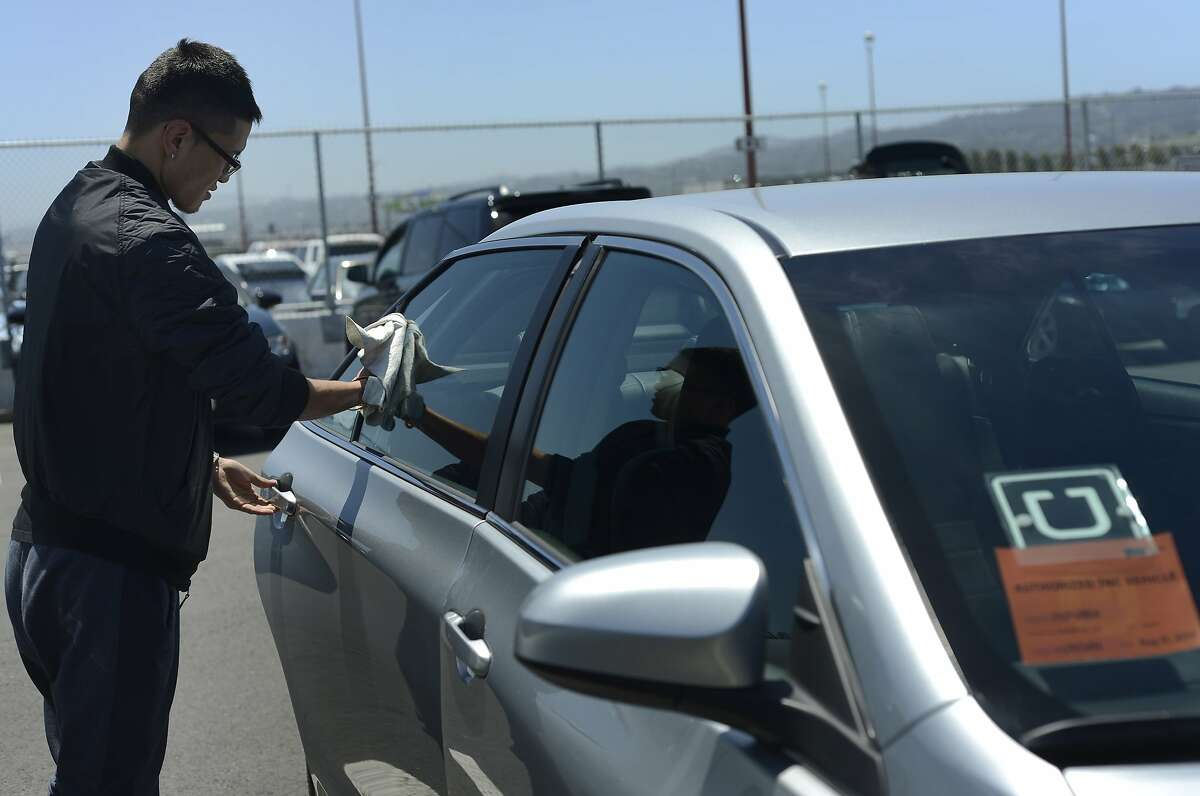 Uber driver Idertsog Darhkan, 23, cleans his car in a parking lot near SFO Airport in San Francisco, California, on Wednesday, June 17, 2015.