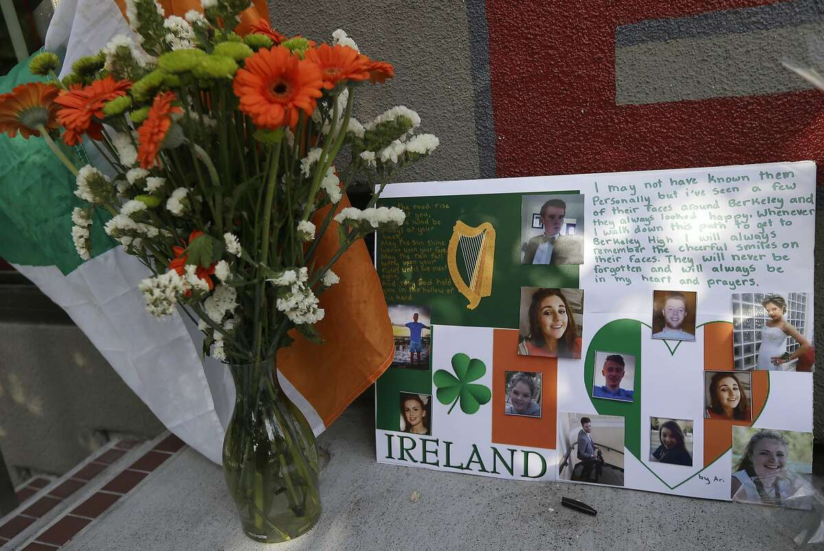 A flag of Ireland, flowers and a sign are shown at a shrine left for victims of the Library Gardens apartment building balcony collapse Wednesday, June 17, 2015. The balcony broke loose from the building during a 21st birthday party early Tuesday, killing several people and seriously injuring others. (AP Photo/Jeff Chiu)